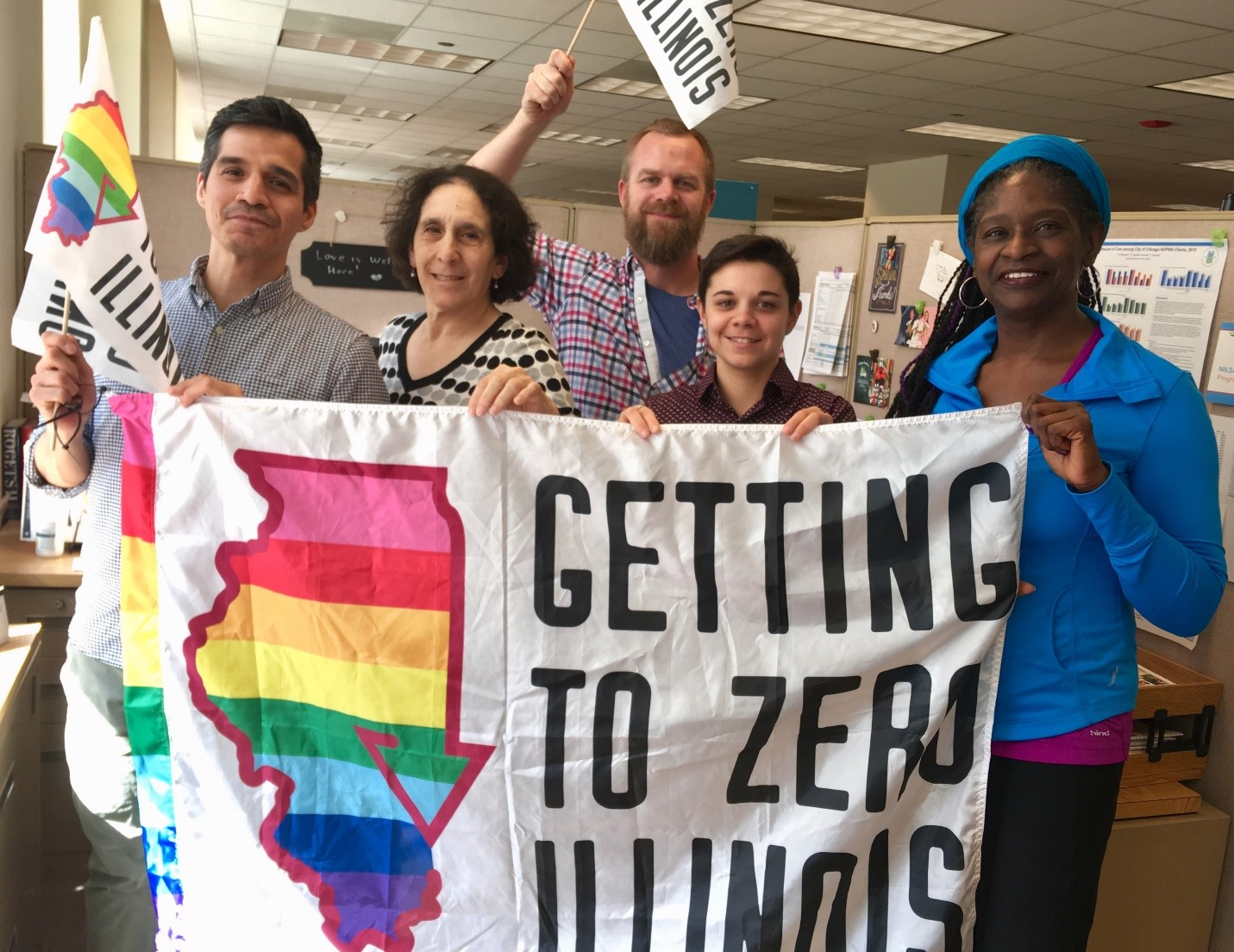 Picture of 5 people who work at Chicago Department of Public Health holding up Getting to Zero Illinois rainbow flags.